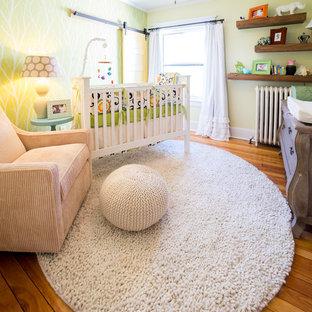 Aménagement d'une petit chambre de bébé neutre classique avec un mur jaune et un sol en bois brun.
