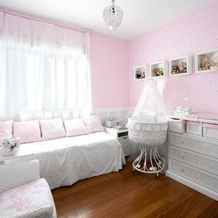 Ejemplo de habitación de bebé niña clásica, de tamaño medio, con paredes rosas y suelo de madera en tonos medios