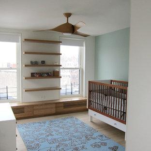 Diseño de habitación de bebé neutra actual, de tamaño medio, con paredes azules y suelo de madera clara