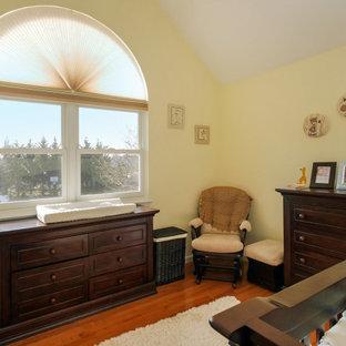 Cette image montre une chambre de bébé garçon de taille moyenne avec un mur jaune, un sol en bois foncé et un plafond voûté.