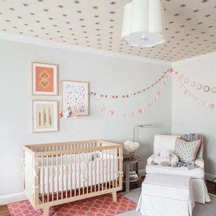 Modelo de habitación de bebé niña clásica renovada, de tamaño medio, con paredes grises y suelo de madera en tonos medios