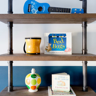 This is an example of a medium sized classic nursery for boys in Orange County with blue walls and carpet.