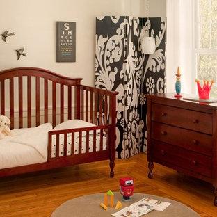 Immagine di una cameretta per neonati neutra tradizionale di medie dimensioni con pareti bianche e pavimento in legno massello medio