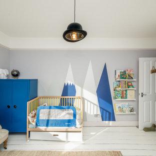 Imagen de habitación de bebé niño actual con paredes grises, suelo de madera pintada y suelo blanco
