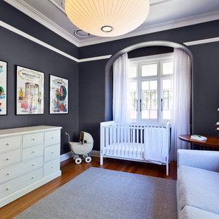 Ejemplo de habitación de bebé neutra tradicional renovada, de tamaño medio, con paredes negras y suelo de madera en tonos medios