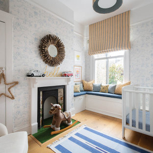 This is an example of a traditional nursery for boys in London with multi-coloured walls and light hardwood floors.