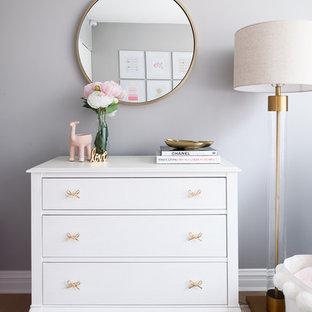 Immagine di una piccola cameretta per neonata classica con pareti grigie, moquette e pavimento rosa