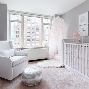 Diseño de habitación de bebé niña tradicional renovada, pequeña, con paredes grises, moqueta y suelo rosa