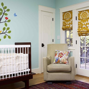 Design ideas for a medium sized eclectic gender neutral nursery in San Francisco with blue walls, light hardwood flooring and brown floors.