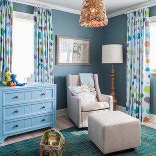 Diseño de habitación de bebé neutra clásica renovada con paredes azules y suelo de madera clara