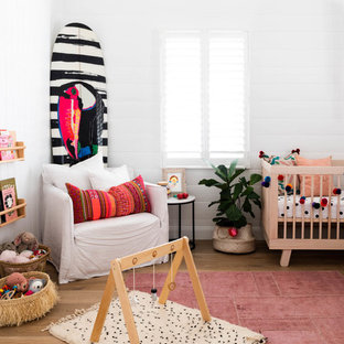 This is an example of a beach style nursery in Brisbane with white walls, medium hardwood floors and brown floor.