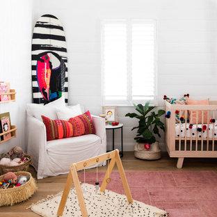 Aménagement d'une chambre de bébé bord de mer avec un mur blanc, un sol en bois brun et un sol marron.