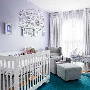 Exemple d'une chambre de bébé fille chic avec un mur violet et un sol en bois brun.