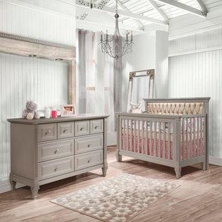 Diseño de habitación de bebé neutra contemporánea con paredes amarillas y suelo de madera clara