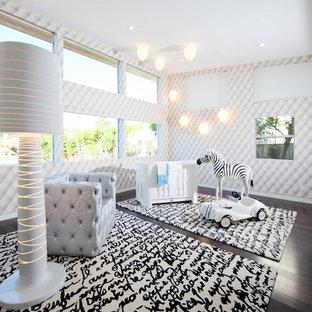 Esempio di una grande cameretta per neonati neutra design con pareti multicolore, parquet scuro e pavimento nero