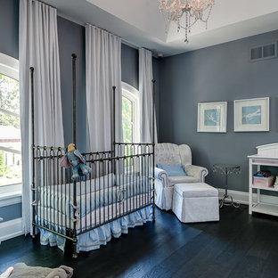 Réalisation d'une grand chambre de bébé neutre tradition avec un mur gris, un sol en bois foncé et un sol noir.