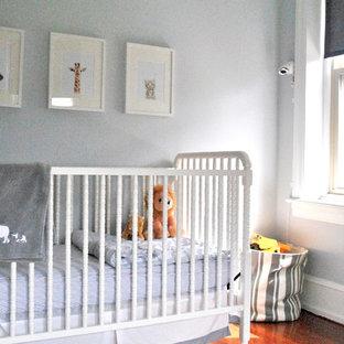 Ejemplo de habitación de bebé neutra minimalista, pequeña, con paredes grises, suelo de madera oscura y suelo marrón