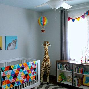Idée de décoration pour une chambre de bébé neutre tradition de taille moyenne avec un mur gris et un sol en bois foncé.
