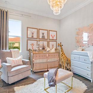 Imagen de habitación de bebé niña moderna, de tamaño medio, con paredes grises, suelo de baldosas de cerámica y suelo gris
