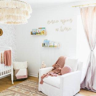 Idées déco pour une chambre de bébé fille campagne de taille moyenne avec un mur blanc, un sol en bois clair et un sol marron.