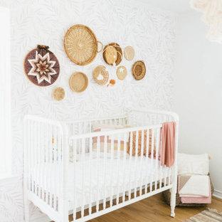 Foto de habitación de bebé niña de estilo de casa de campo, de tamaño medio, con paredes blancas, suelo de madera clara y suelo marrón