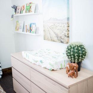 Cette image montre une chambre de bébé garçon sud-ouest américain de taille moyenne avec un mur blanc, un sol en bois foncé et un sol marron.