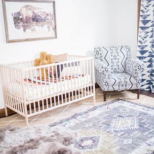 Aménagement d'une chambre de bébé garçon sud-ouest américain de taille moyenne avec un mur blanc, un sol en bois foncé et un sol marron.