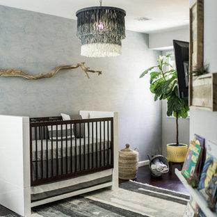 Medium sized beach style nursery for boys in Philadelphia with grey walls, dark hardwood flooring and brown floors.
