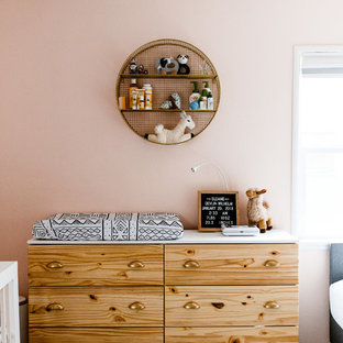 Inspiration for a small bohemian nursery for girls in Los Angeles with pink walls and laminate floors.