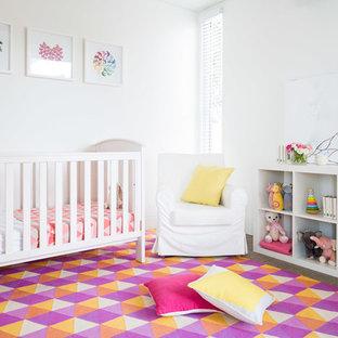 Idées déco pour une chambre de bébé fille contemporaine de taille moyenne avec un mur blanc, moquette et un sol multicolore.