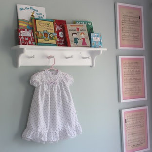Example of a mid-sized classic girl medium tone wood floor nursery design in Orange County with gray walls