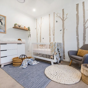 This is an example of a contemporary gender-neutral nursery in Other with white walls, carpet and beige floor.