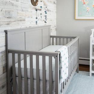 Esempio di una cameretta per neonato industriale di medie dimensioni con pareti grigie e pavimento in legno massello medio