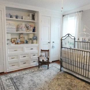Cette photo montre une chambre de bébé neutre chic de taille moyenne avec un mur gris et un sol en bois brun.