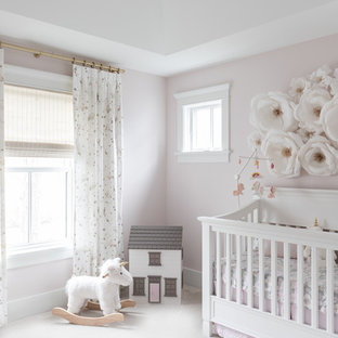 Aménagement d'une grand chambre de bébé fille campagne avec un mur rose, moquette et un sol blanc.