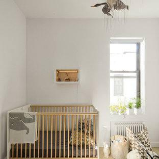 Inspiration for a small gender-neutral medium tone wood floor nursery remodel in New York with white walls