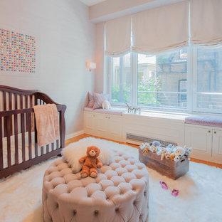 Idée de décoration pour une chambre de bébé fille tradition de taille moyenne avec un mur violet et un sol en bois brun.