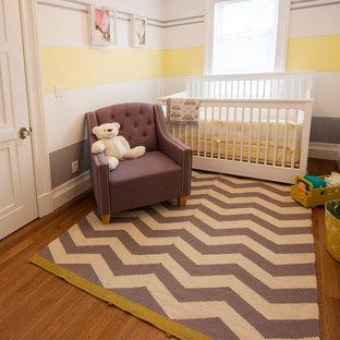 Imagen de habitación de bebé neutra tradicional renovada, pequeña, con paredes amarillas y suelo de madera en tonos medios