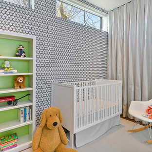 Contemporary gender neutral nursery in Chicago with multi-coloured walls and medium hardwood flooring.