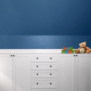 Diseño de habitación de bebé niño clásica renovada, de tamaño medio, con paredes azules y suelo de madera oscura