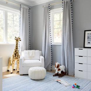 Modelo de habitación de bebé neutra costera, de tamaño medio, con paredes grises y suelo de madera clara