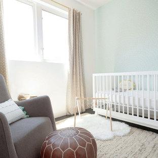 Ejemplo de habitación de bebé neutra moderna, de tamaño medio, con suelo de madera oscura, suelo marrón y paredes blancas