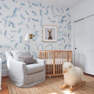 Modelo de habitación de bebé neutra tradicional renovada, de tamaño medio, con suelo de madera en tonos medios y paredes multicolor