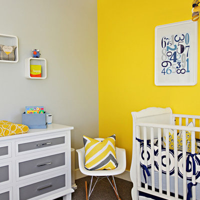 Trendy gender-neutral carpeted nursery photo in Orange County with yellow walls