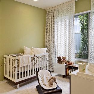 Ejemplo de habitación de bebé neutra actual con paredes verdes