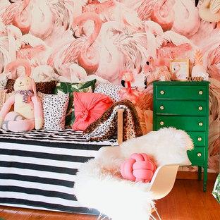 Idées déco pour une chambre de bébé fille exotique avec un mur rose, un sol en bois brun et un sol marron.