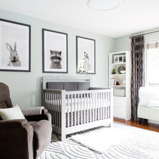 Photo of a medium sized classic nursery for boys in Toronto with green walls and light hardwood flooring.