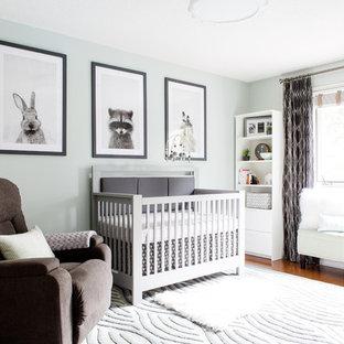 Esempio di una cameretta per neonato classica di medie dimensioni con pareti verdi e parquet chiaro
