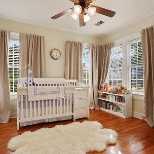 Cette image montre une chambre de bébé neutre traditionnelle avec un mur beige, un sol en bois brun et un sol orange.