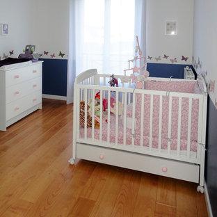 Diseño de habitación de bebé niña tradicional, de tamaño medio, con paredes multicolor y suelo de madera clara
